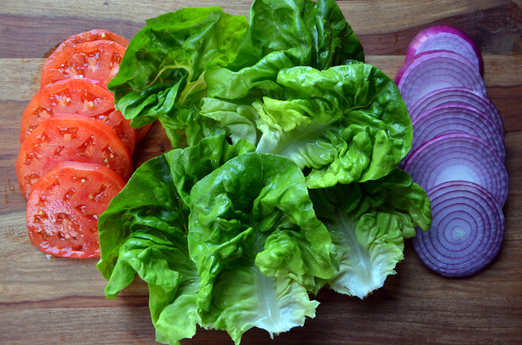 Burger toppings: lettuce, tomato and red onion.